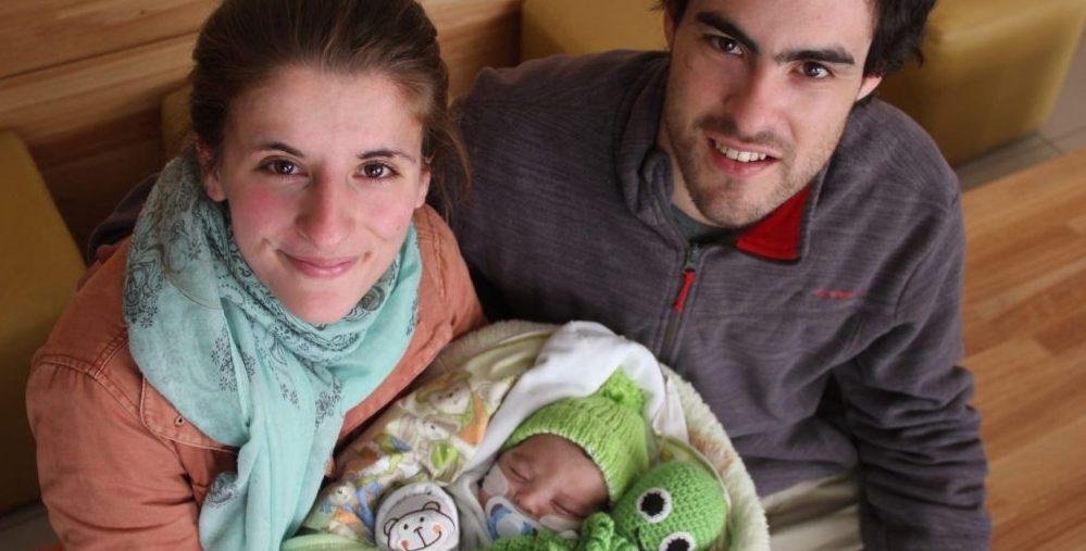 Mamá y papá sonrien junto a su bebé al ser dado de alta