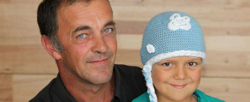 Padre y su hija sonríen. Ella lleva puesto un sombrero tejido en lana azul.