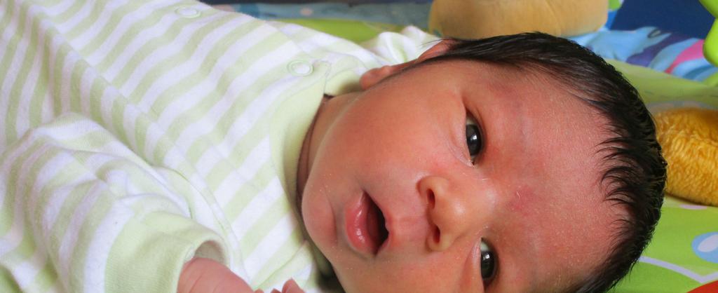 Bebé acostado con sus bracitos extendidos.