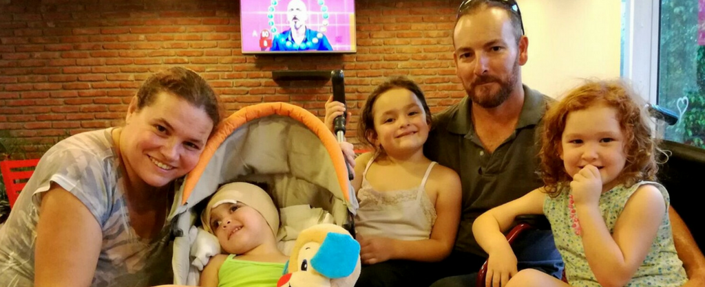 Padre, madre y tres hijas. Una de ellas, tiene un vendaje en su cabeza, se encuentra acostada en un cochecito.