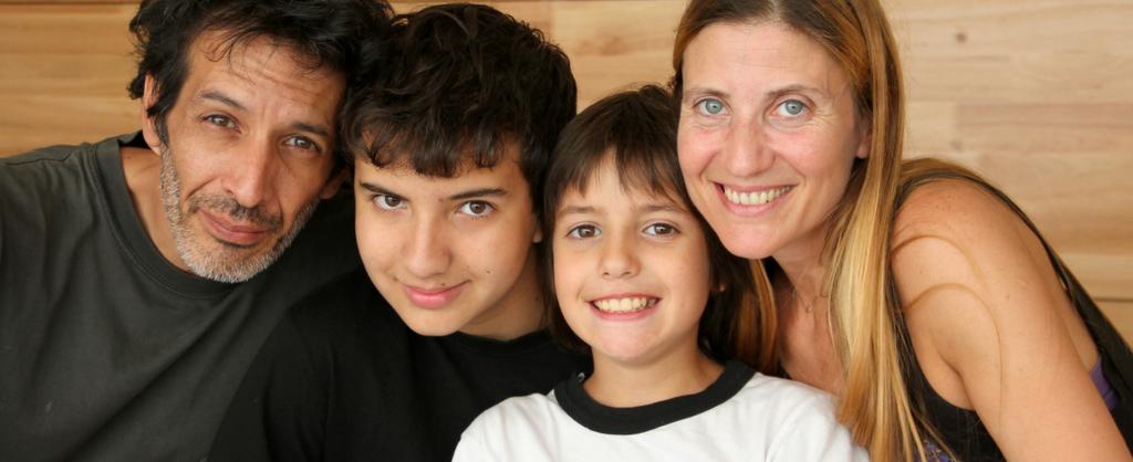 Padre y madre con sus dos hijos en medio de los dos.