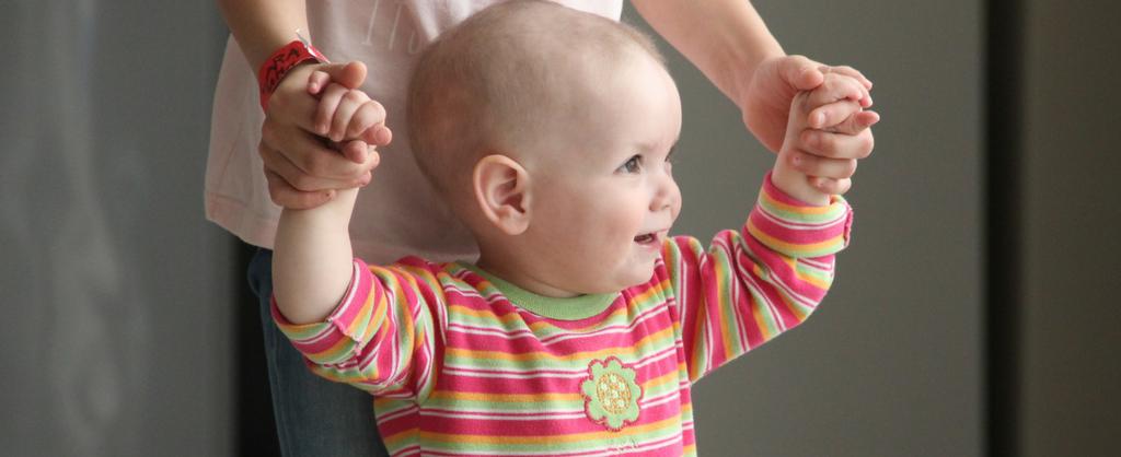 Pequeña niña sosteniendo las manos de su madre, intentando dar sus primeros pasos.