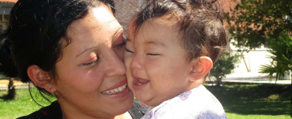 Madre sonríe mientras sostiene a su bebe cerquita de su cara. El bebé ríe.