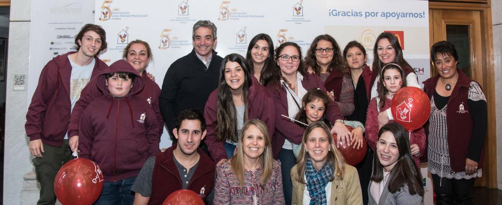 Grupo de jóvenes, niños y adultos reunidos, muy sonrientes, frente a una pancarta con el logo de la Logo de la Asociación Casa Ronald McDonald Uruguay..