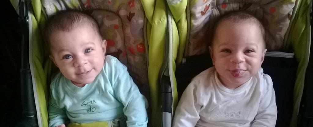 Bebes gemelos sentados en sus coches sonriendo.