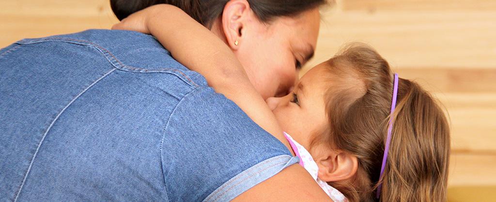 Madre abrazando a su pequeña hija.